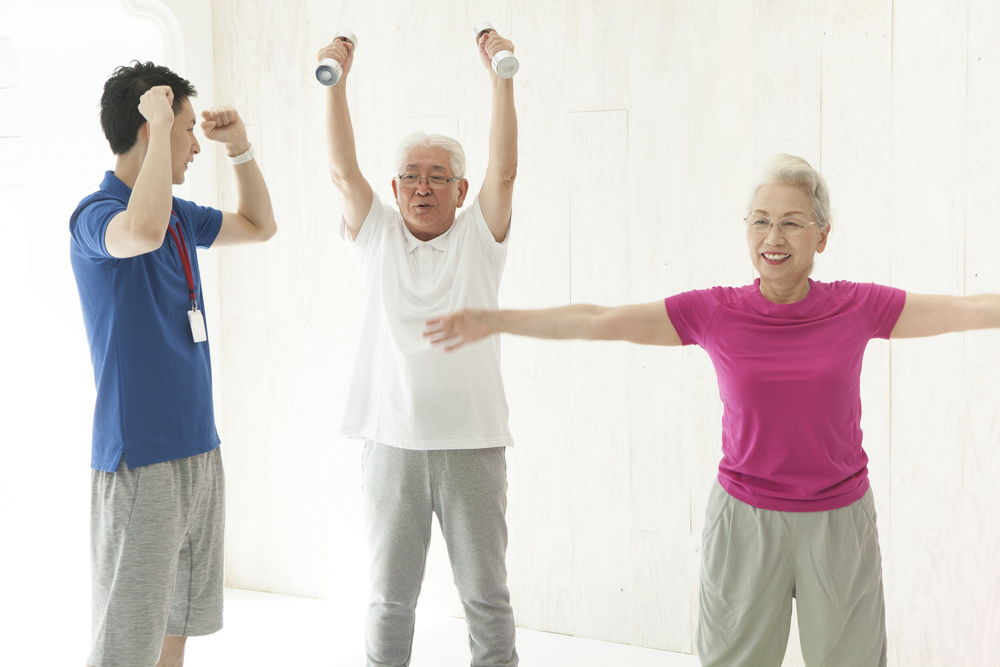 An old couple is doing dumbbell training with a trainer