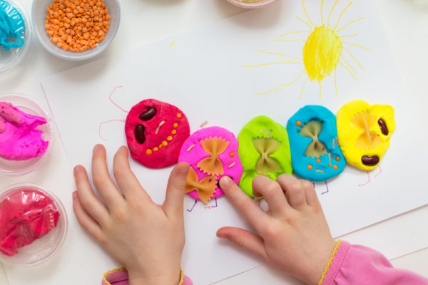 Little girl playing with plasticine. Play clay caterpillar decorated with cereals. Creative learning activities