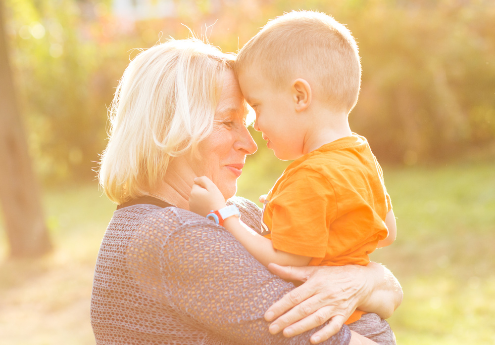 Portrait of happy grandmother with grandson embracing outdoor