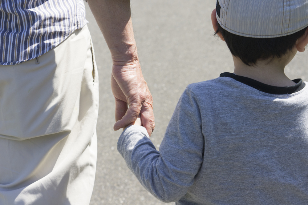Child and senior man holding hands