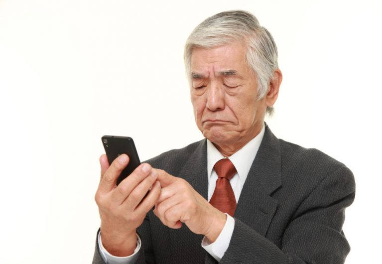 senior Japanese businessman using smart phone looking confused