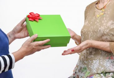 Elderly woman receiving a gift from daughter