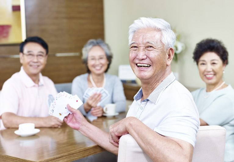 senior asian man in playing cards with friends