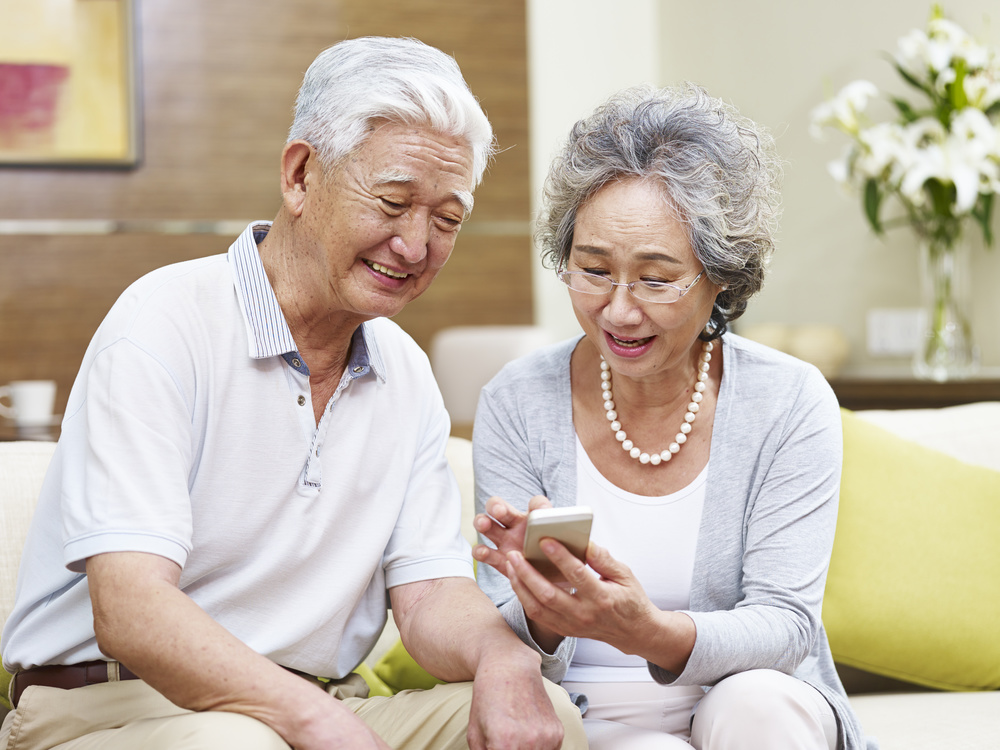 senior asian couple using cellphone at home