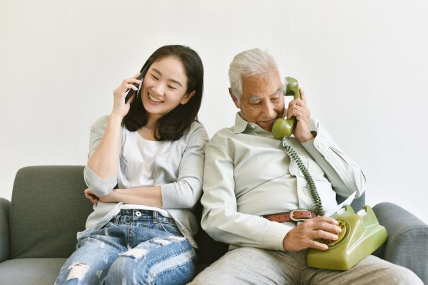 Happy family relationship, Asian elderly old father and smiling daughter make a phone call to each other, Communication in difference technology generations, Smartphone and telephone.