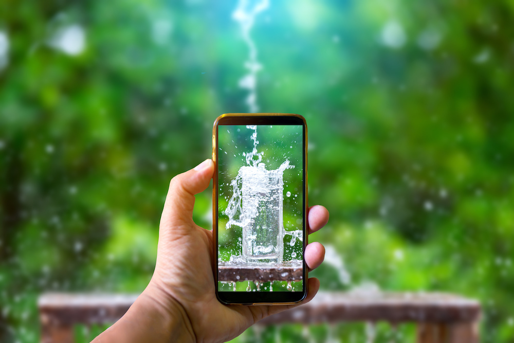 Hand holding mobile phone and take a photo Drink water pouring in to glass over sunlight and natural green background.Water splash in glass Select focus blurred background.