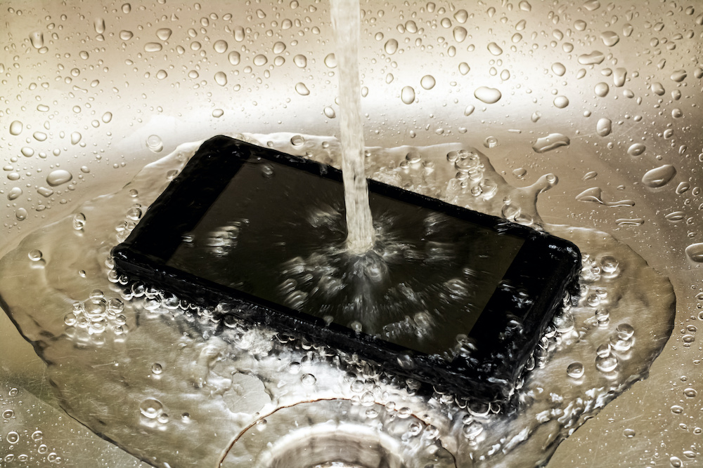 Touch mobile phone under tap water close up