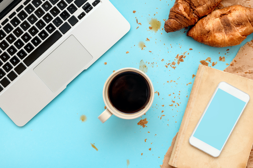 Coffee and croissants for messy breakfast in business office