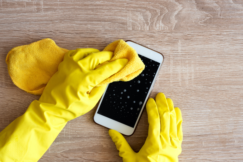 Female hand in rubber protective glove with rag wiping smartphone using cleaning spray.