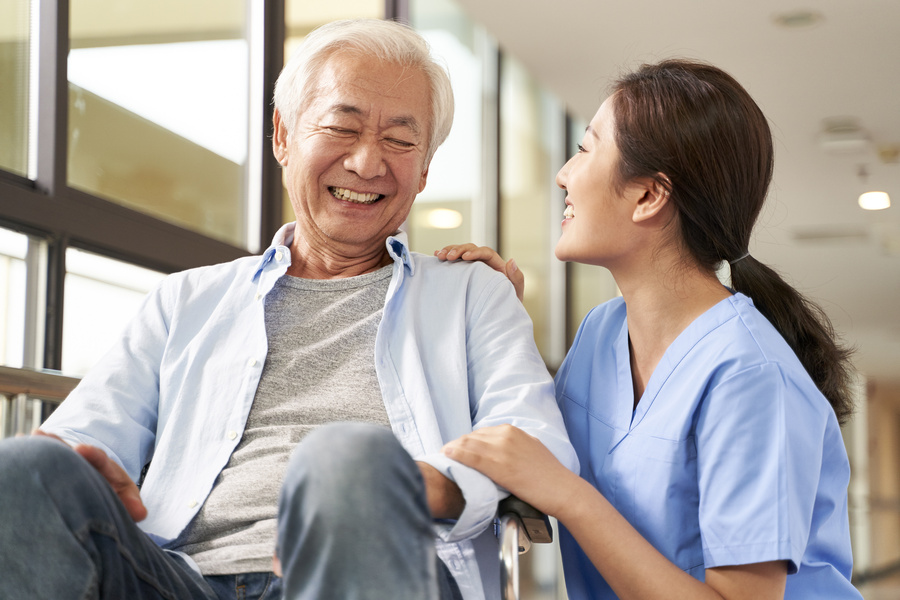 young friendly asian female caregiver talking to elderly man in nursing home