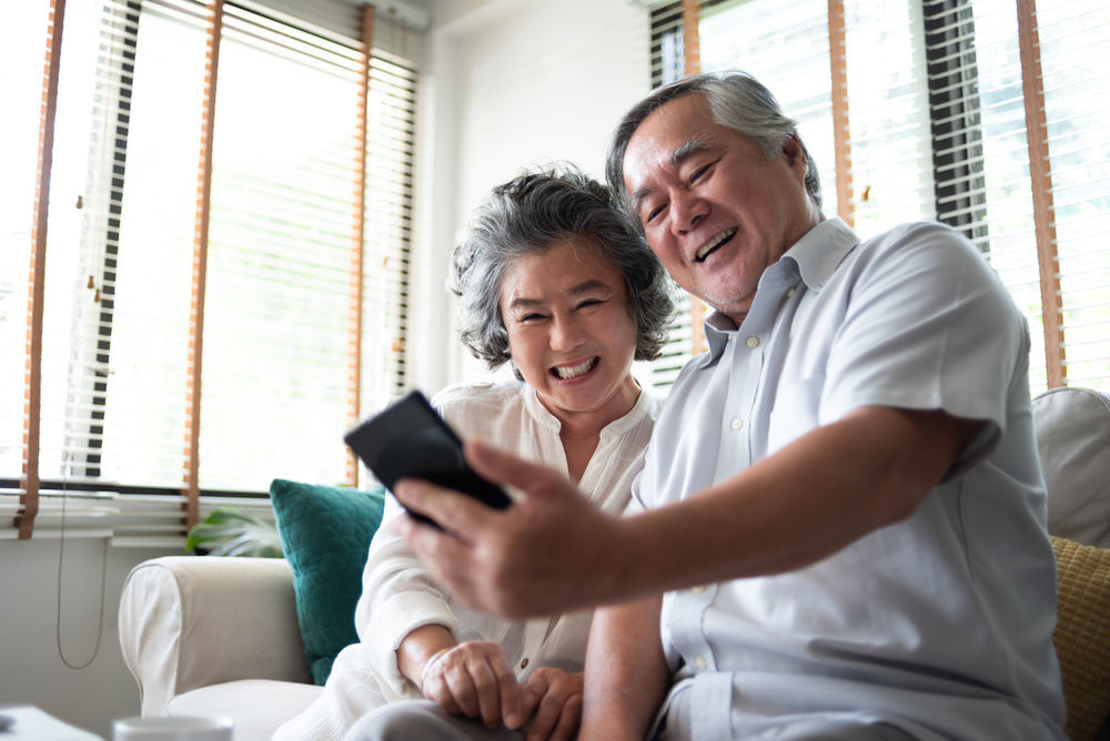 Happy Asian senior Couple using smartphone.