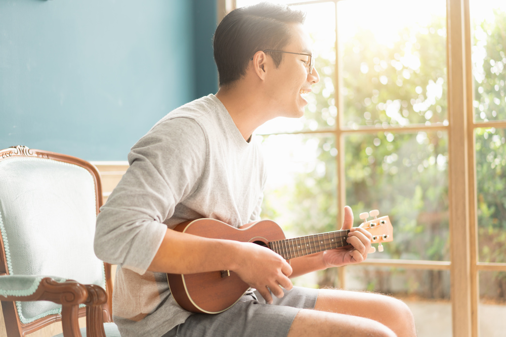 Asian young man hands playing acoustic guitar ukulele at home. Enjoy playing acoustic guitar sunshine in the evening..