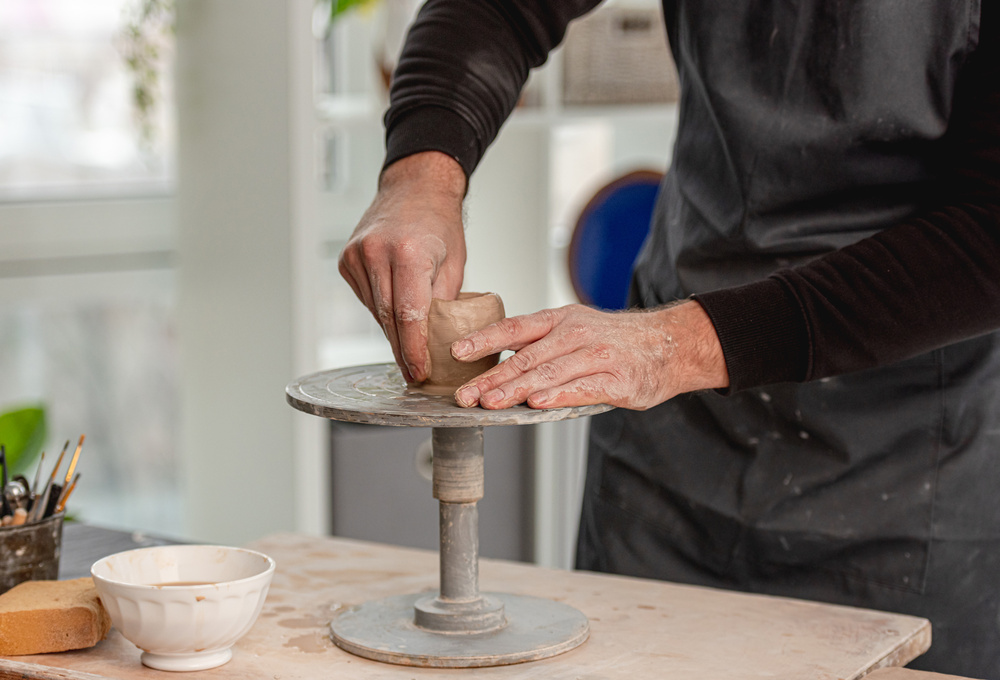 Man using pottery wheel for molding