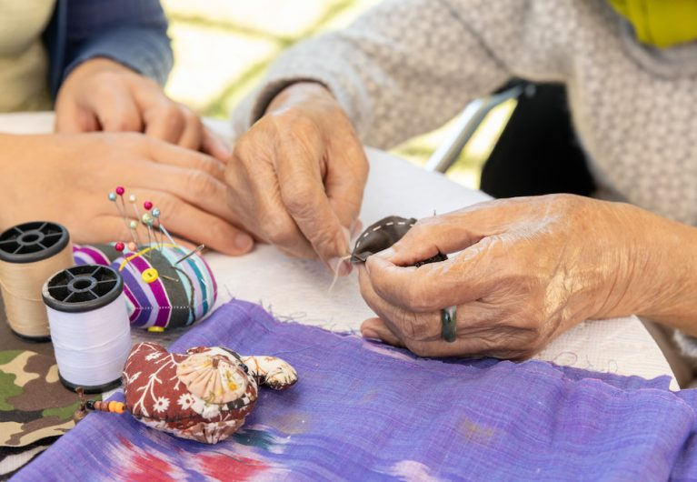 Elderly woman and daughter in the needle crafts occupational therapy for Alzheimer's or dementia