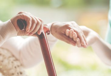 Closeup of senior lady holding walking stick in one hand and holding nurse's hand in the other