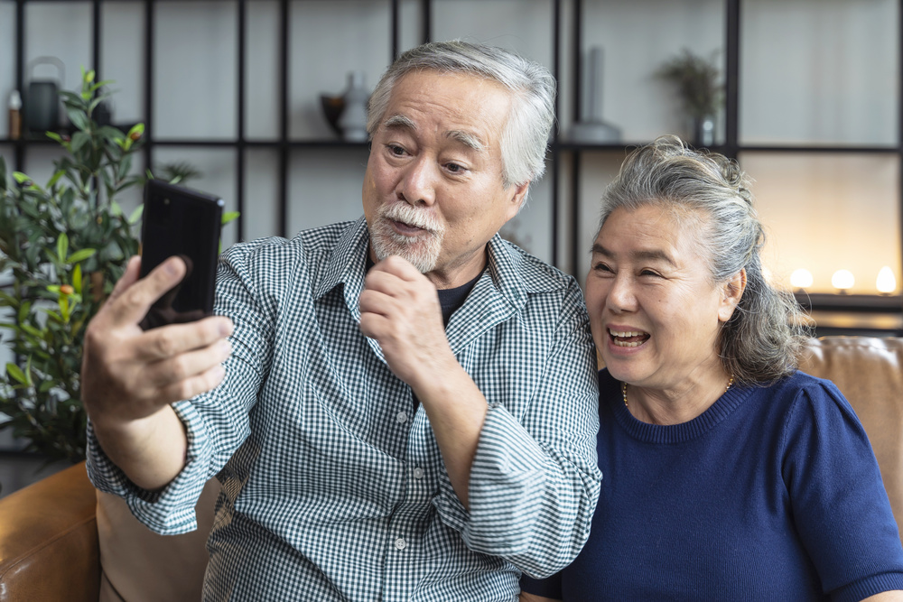 happiness asian old senior retired couple enjoy videocall to family together on sofa in living room at home,asian people use smartphone communication to family home isolation ides concept