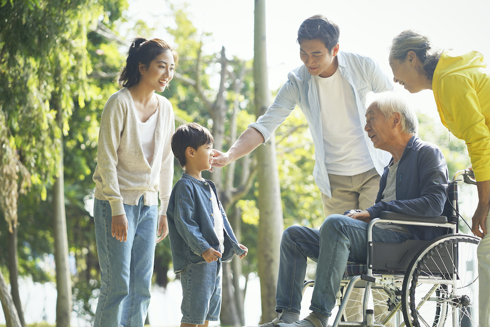 happy asian multi generation family relaxing outdoors